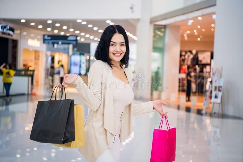 Portret van mooie jonge vrouw met het winkelen zakken die op shopping spree uitgaan stock foto