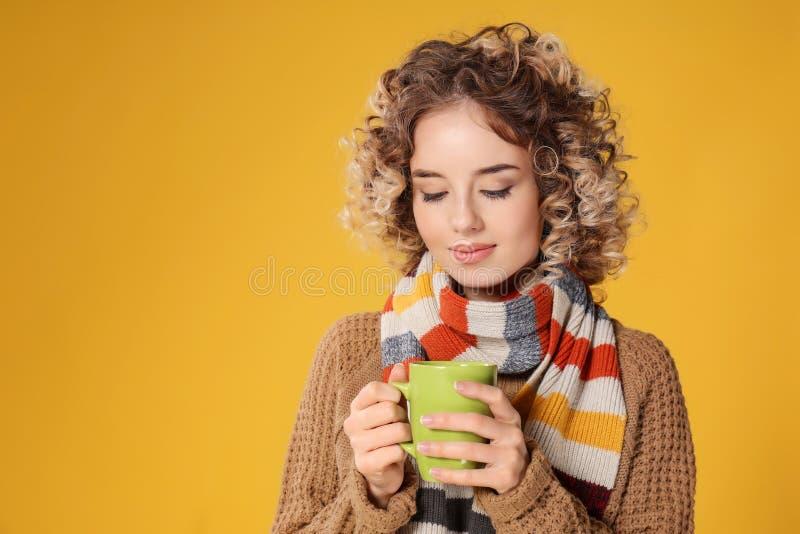 Portret van mooie jonge vrouw met kop van hete koffie op kleurenachtergrond stock foto