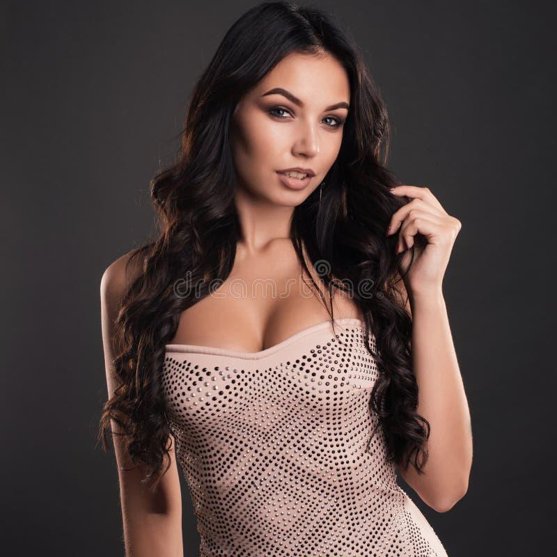 Portret van mooie jonge vrouw met lang haar in een strakke glanzende kleding stock afbeelding