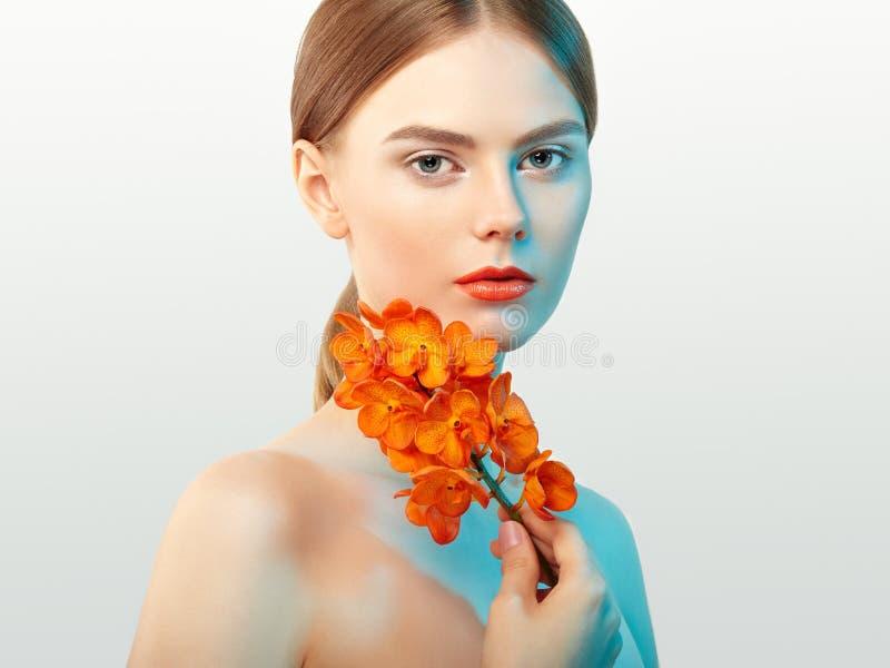 Portret van mooie jonge vrouw met orchidee stock afbeeldingen