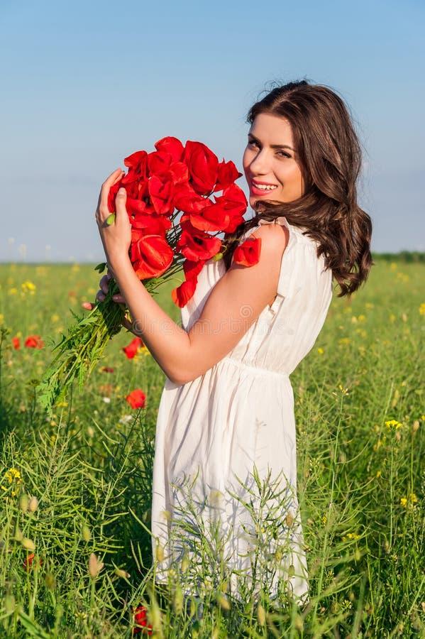 Portret van mooie jonge vrouw met papavers op het gebied met een papaversboeket stock foto