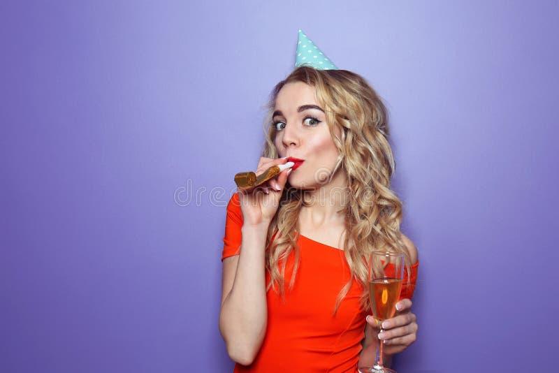 Portret van mooie jonge vrouw met partijfluitje en glas champagne op kleurenachtergrond stock fotografie