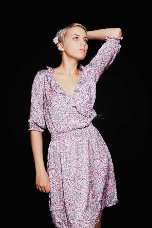 Mooie jonge vrouw in sering sundress op zwarte achtergrond royalty-vrije stock afbeelding