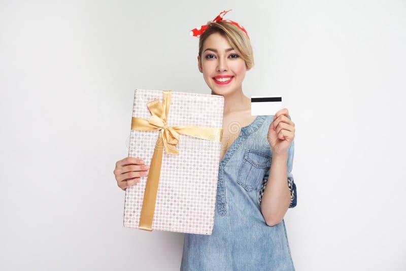 Portret van mooie jonge vrouw in toevallig blauw denimoverhemd met make-up en rode hoofdband die, tonend giftdoos en krediet bevi stock afbeeldingen