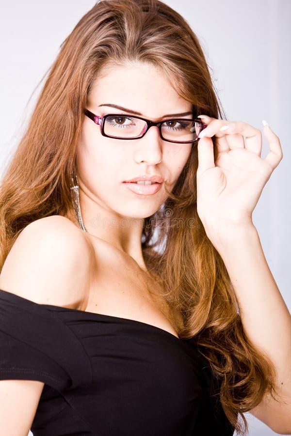 Portret van mooie jonge vrouw wat betreft haar gla stock fotografie
