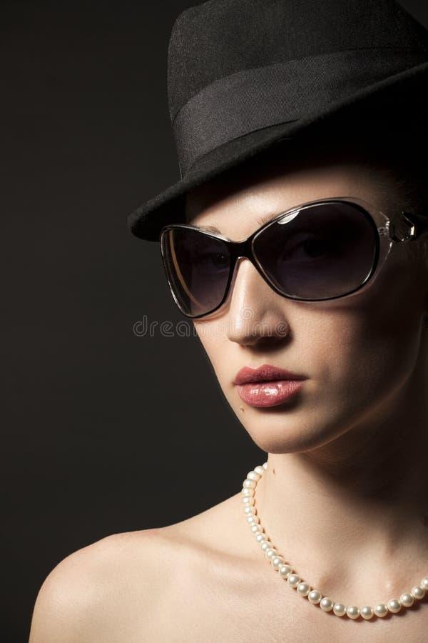 Portret van Mooie jonge vrouw in zwarte hoed en zonnebril stock foto
