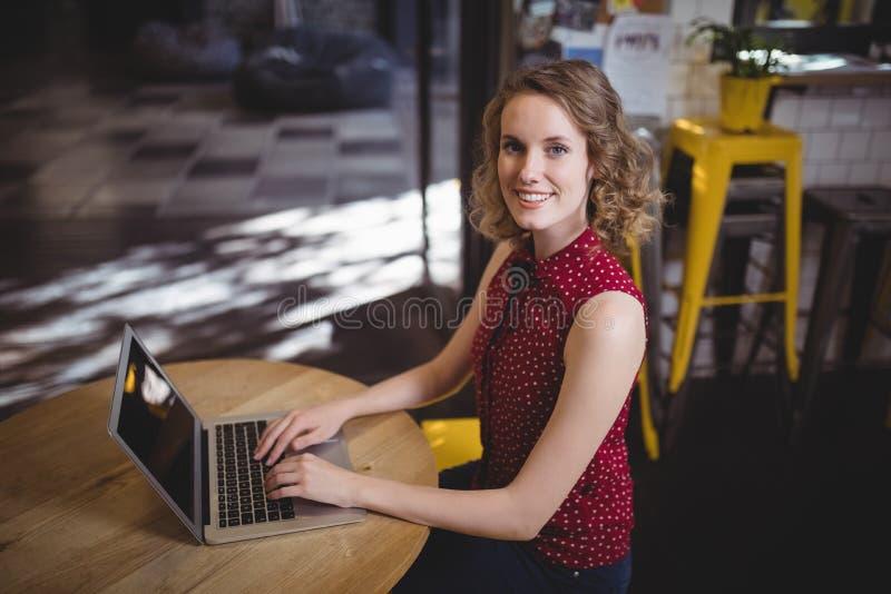 Portret van mooie jonge vrouwelijke klantenzitting met laptop bij lijst royalty-vrije stock afbeelding