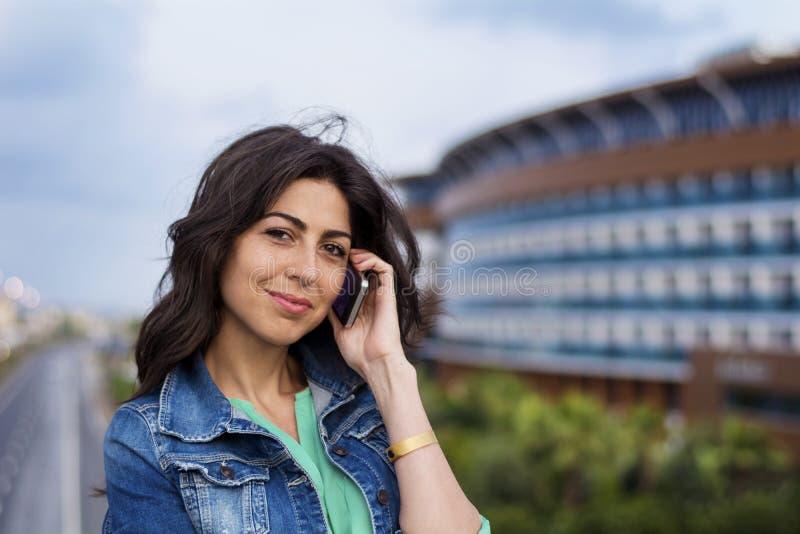 Portret van mooie jonge vrouwenzitting op de brug over de weg en het spreken op de telefoon royalty-vrije stock afbeelding