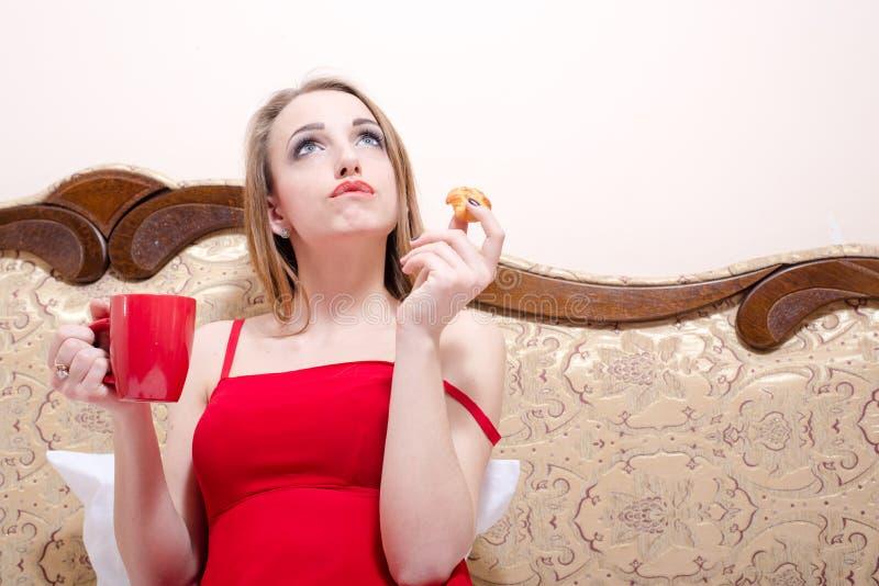 Portret van mooie jonge vrouwenzitting op wit bed in rode kleding het drinken thee en het eten van cake stock foto's