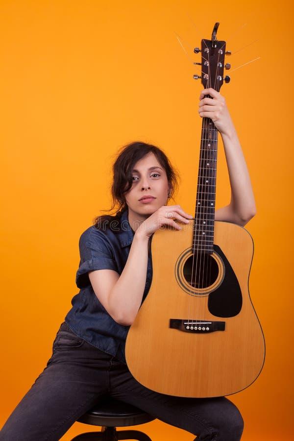 Portret van mooie jonge zanger die haar acustic gitaar in studio over gele achtergrond houden royalty-vrije stock foto's