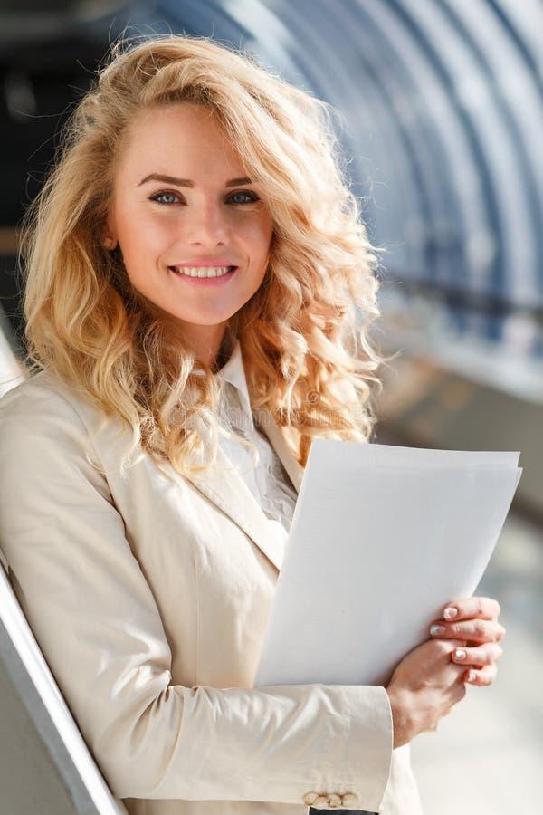 Portret van mooie Kaukasische glimlachende vrouw met documenten Bedrijfs concept royalty-vrije stock afbeelding