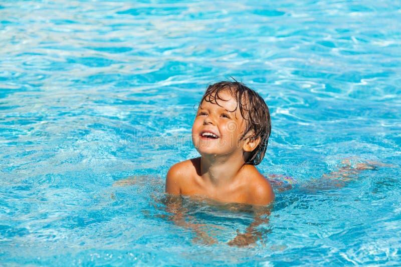 Portret van mooie kleine lachende jongen in water stock foto's