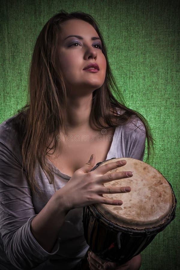 Mooie vrouw het spelen djembe trommel stock afbeelding