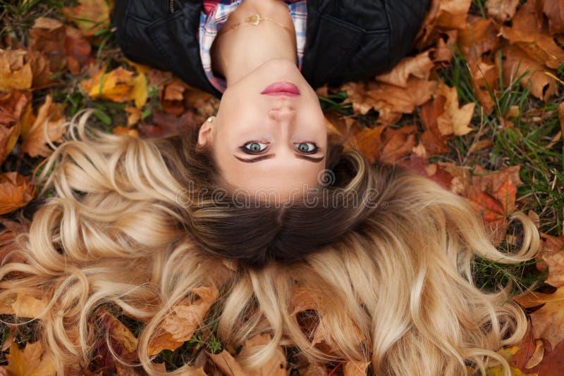 Portret van mooie leuke blonde jonge vrouw Het stellen op de gouden achtergrond van de de herfstaard De foto van de manier royalty-vrije stock afbeeldingen