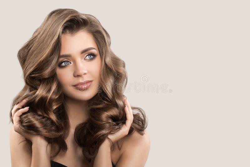 Portret van mooie leuke vrouw met krullend bruin lang haar stock fotografie