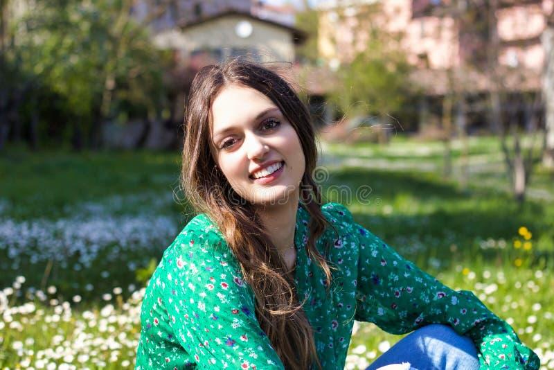 Portret van mooie meisje het glimlachen zitting op een gebied van madeliefjes royalty-vrije stock foto's