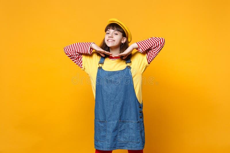 Portret van mooie meisjestiener in Franse baret, denim die sundress die handen houden dichtbij gezicht op gele muur wordt geïsole stock afbeelding