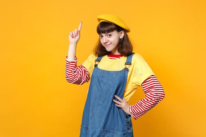Portret van mooie meisjestiener in Franse baret, denim die sundress die wijsvinger richten omhoog op gele muur wordt geïsoleerd stock foto's