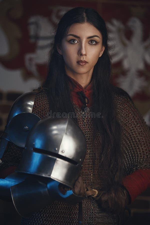 Portret van mooie middeleeuwse meisjesstrijder in een chainmailkap met helm in handen royalty-vrije stock afbeelding