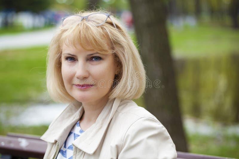 Portret van mooie midden oude vrouw in het de zomerpark royalty-vrije stock fotografie