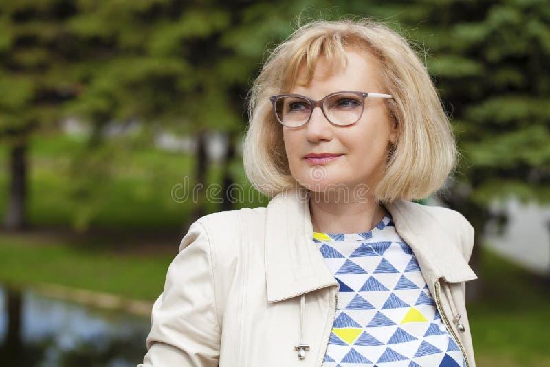 Portret van mooie midden oude vrouw in het de zomerpark stock fotografie