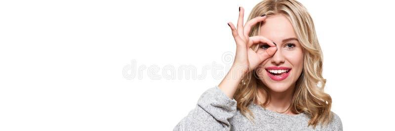 Portret van mooie opgewekte vrouw in toevallige kleding die en o.k. die teken glimlachen tonen bij camera over witte achtergrond  royalty-vrije stock afbeelding