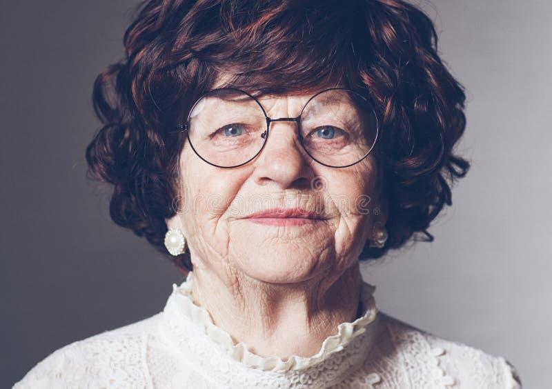 Portret van mooie oude volwassen vrouw in glazen, 80 jaar oud stock fotografie