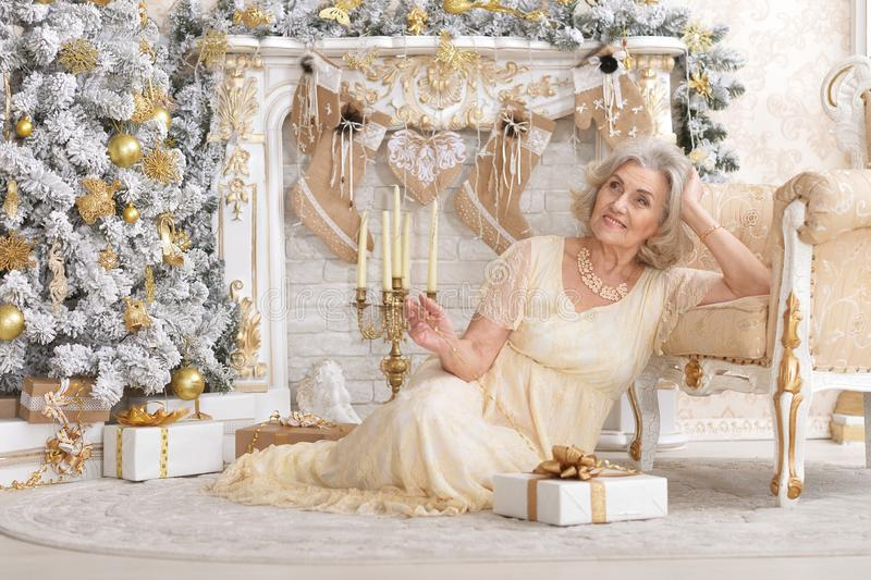Portret van mooie rijpe die vrouwenzitting dichtbij stoel met giftdoos in ruimte aan Kerstmisvakantie wordt verfraaid royalty-vrije stock afbeelding