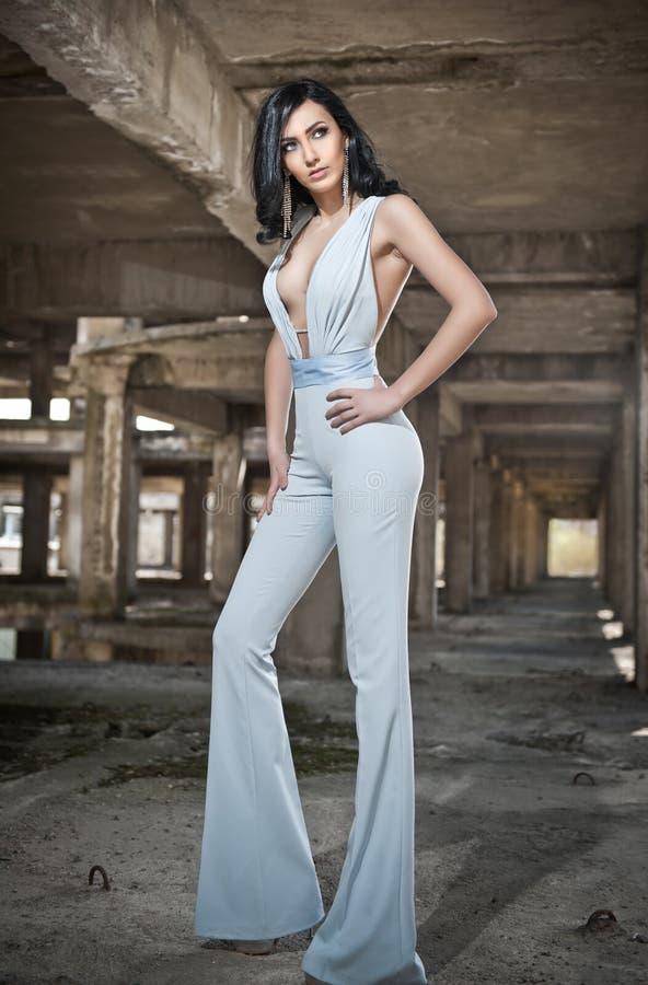 Portret van mooie sexy jonge vrouw met elegante algemeen, op stedelijke achtergrond Aantrekkelijk jong brunette met lang haar royalty-vrije stock foto