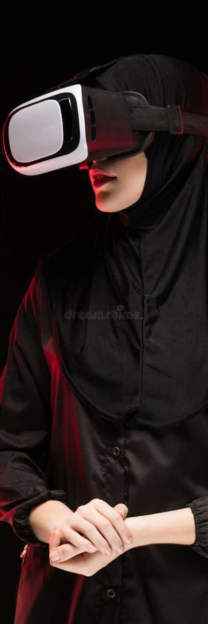 Portret van mooie slimme jonge moslimvrouw die zwarte hijab dragen die virtuele werkelijkheidshoofdtelefoon op zwarte achtergrond royalty-vrije stock afbeelding