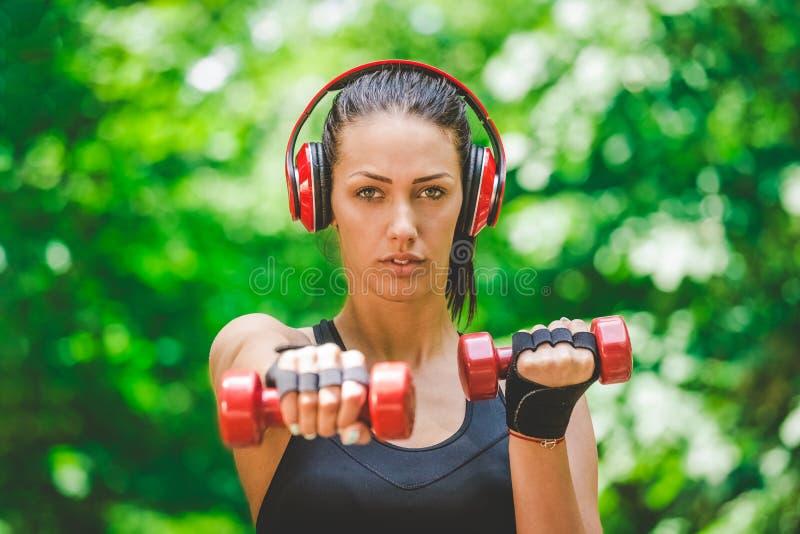 Portret van mooie sportvrouw die met kleine gewichten in het park uitoefenen royalty-vrije stock foto's