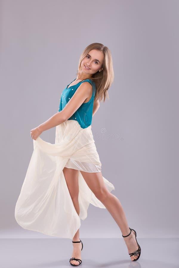 Portret van mooie tiener in witte en blauwe kleding over grijze achtergrond royalty-vrije stock fotografie