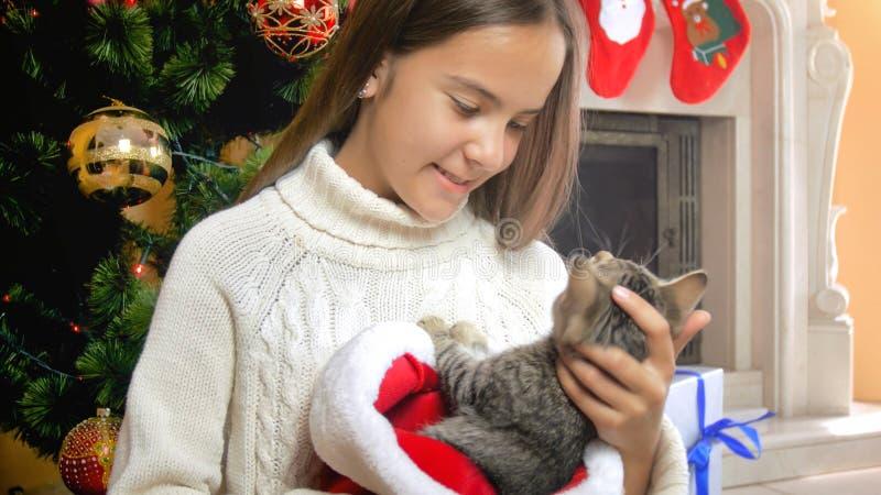Portret van mooie tiener in wollen swweater die katje koesteren onder Kerstboom stock afbeeldingen