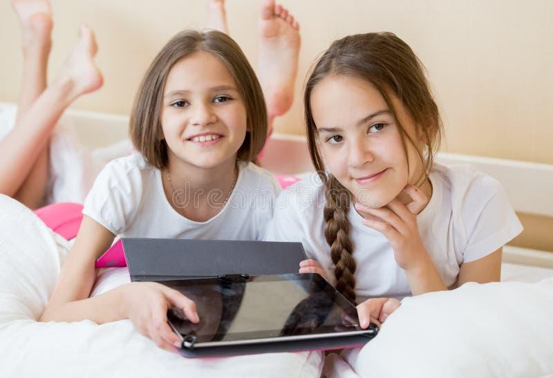 Portret van mooie tieners die op bed liggen en digitale tabletcomputer houden stock afbeeldingen