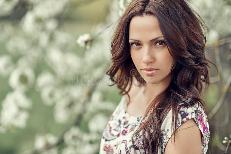 Portret van mooie vrouw in bloeiende boom in de lente stock fotografie