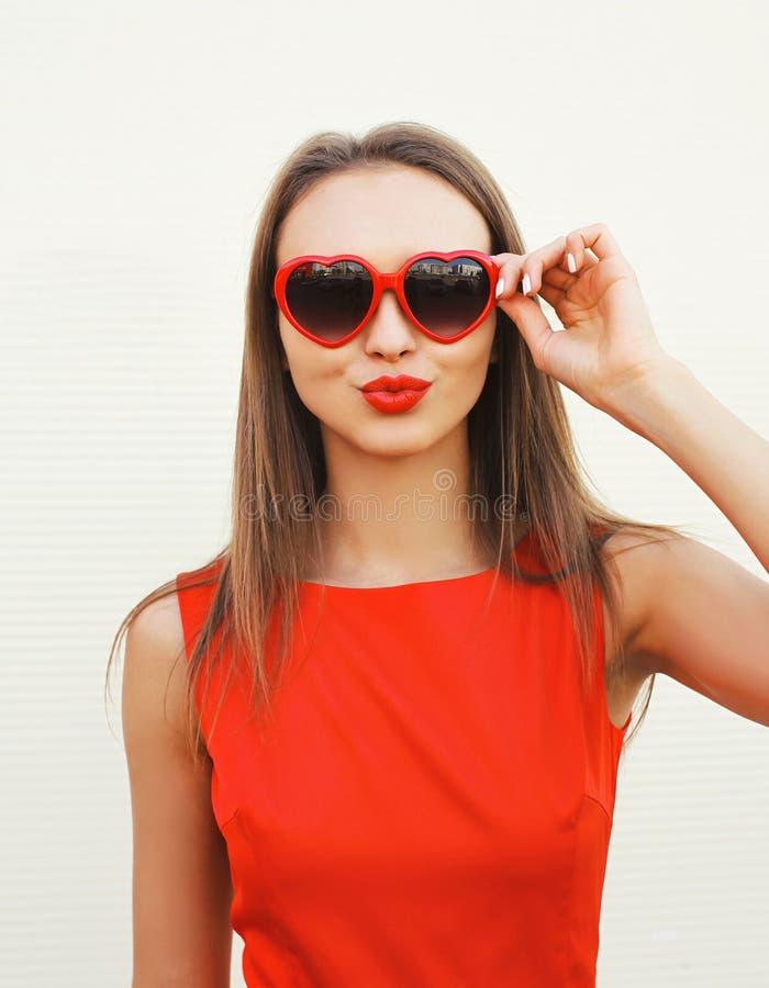 Portret van mooie vrouw in de rode zonnebril die lippenhavi blazen stock fotografie
