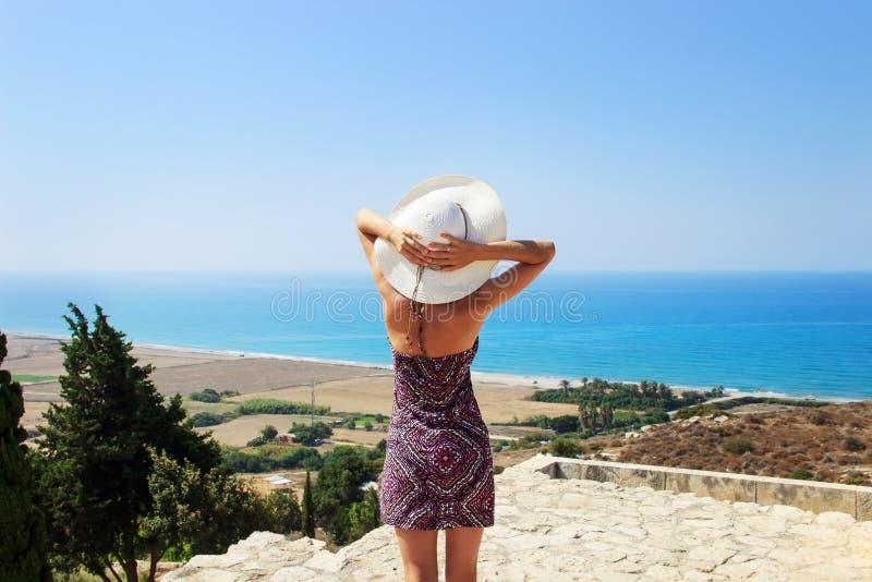 Portret van mooie vrouw die het brede hoed ontspannen aan de overzeese kant dragen royalty-vrije stock foto