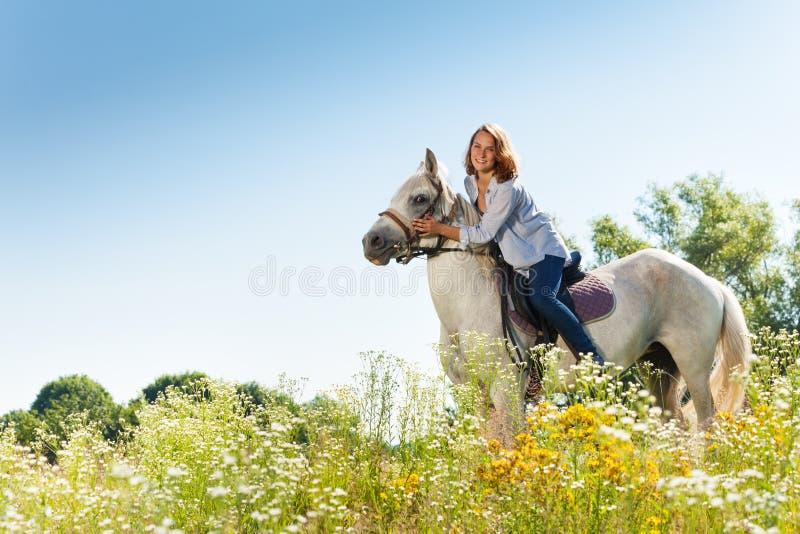 Portret van mooie vrouw die wit paard koesteren stock fotografie