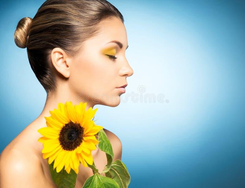 Portret van mooie vrouw en een zonnebloem over blauwe achtergrond Het concept van de lente royalty-vrije stock foto's