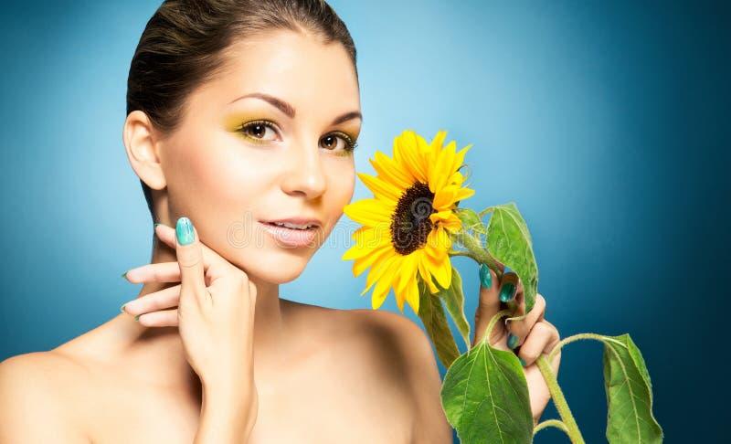 Portret van mooie vrouw en een zonnebloem over blauwe achtergrond Het concept van de lente royalty-vrije stock afbeeldingen