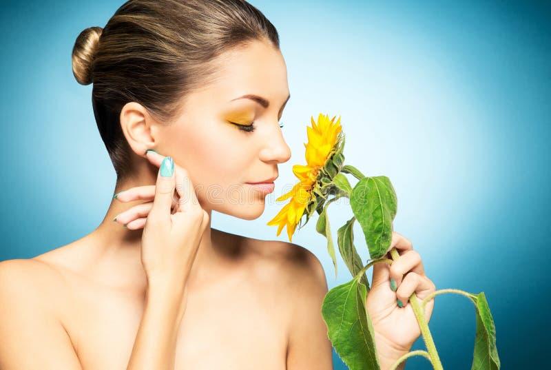Portret van mooie vrouw en een zonnebloem over blauwe achtergrond Het concept van de lente stock foto