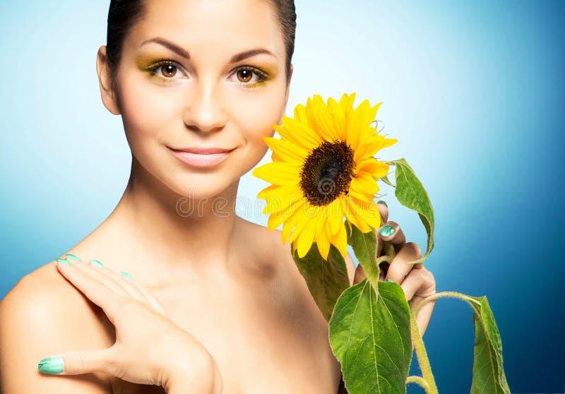Portret van mooie vrouw en een zonnebloem over blauwe achtergrond Het concept van de lente royalty-vrije stock foto