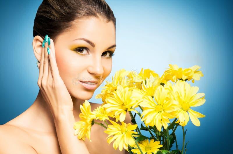 Portret van mooie vrouw en een zonnebloem over blauwe achtergrond Het concept van de lente stock afbeelding