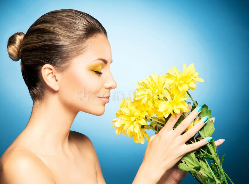 Portret van mooie vrouw en een zonnebloem over blauwe achtergrond Het concept van de lente stock afbeeldingen