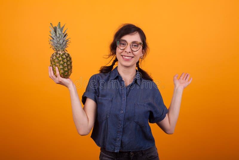 Portret van mooie vrouw met glazen die bij de camera glimlachen en een heerlijke ananas in studio over geel houden stock foto's