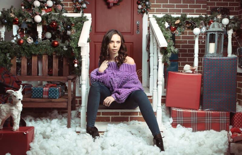 Portret van mooie vrouw met make-up, in gebreide, purpere overmaatse sweater, die over Kerstmis binnenlandse achtergrond stellen stock afbeeldingen