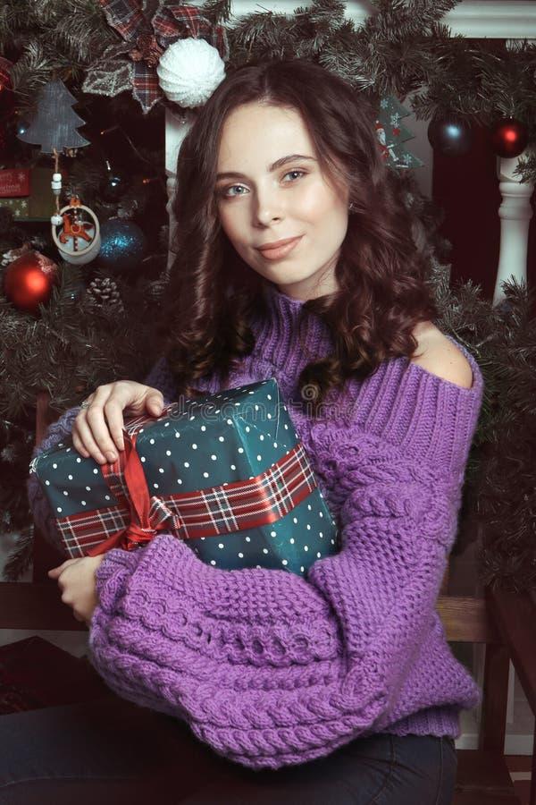 Portret van mooie vrouw met make-up, in gebreide, purpere overmaatse sweater, die over Kerstmis binnenlandse achtergrond met a st royalty-vrije stock foto's