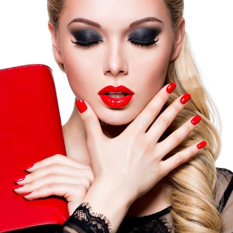 Portret van mooie vrouw met rode lippen en spijkers stock afbeelding