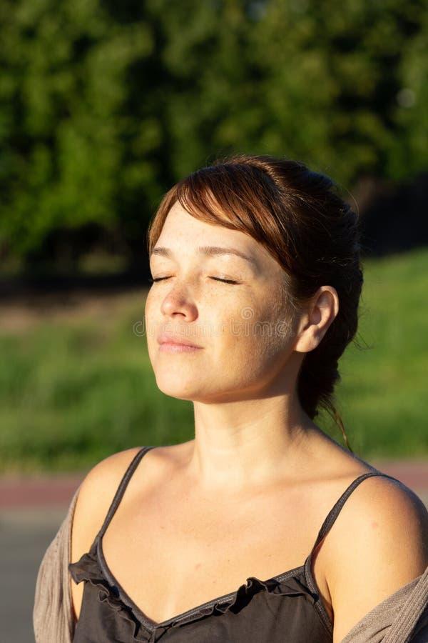 Portret van mooie vrouw op middelbare leeftijd met kalm gezicht met gesloten ogen in de zomer groen park stock foto
