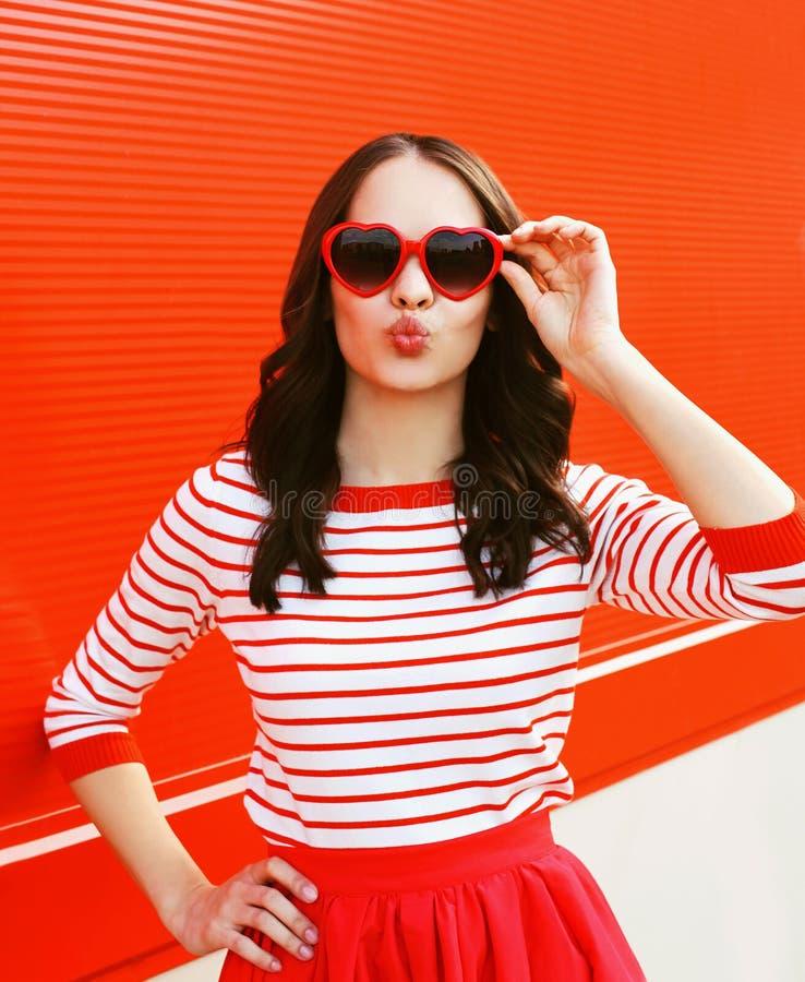 Portret van mooie vrouw in rode zonnebril die lippen blazen stock afbeelding